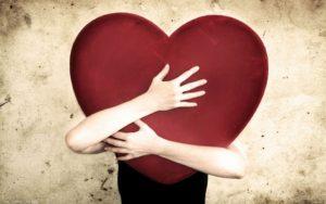 mujejr abrazando un gran corazón rojo
