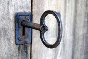Detalle de llave antigua de hierro sobre herraje en puerta de madera