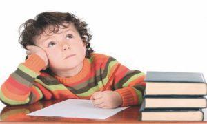 niño distraido con con papel y lapiz y libros