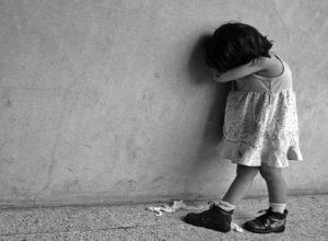 niña llora sola frente a pared y se tapa la cara