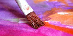 Pincel sobre hoja con colores lilas y violetas
