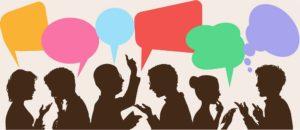 Dbujo de siluetas de personas hablando de perfil con viñetas de colores de diferentes formas, en señal de entendimiento