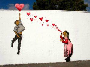 dibujo en la pared de una niña y un niño., la liña le sopla corazones y el niño coge uno y se eleva con él como si fuera un globo