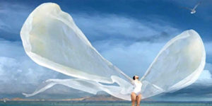 Mujer con alas fondo mar y horizonte