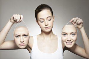 mujer joven con dos máscaras de su propia cara, una enfadada y otra sonriente