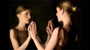 mujer jove se mira al espejo y pione sus manos en él
