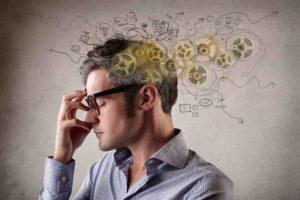hombre joven con gafas que se toca la frente, con un montón de cosas alrrededor de su cabeza en señal de preocupación