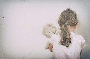 niña con su peluche contra la pared y cabizbajaa