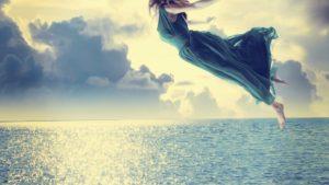 mujer volando entre las nuves por encima del mar