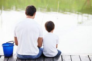 padre e hijo pequeño de espaldas pescando