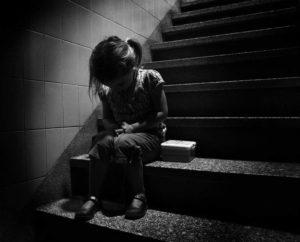 blanco y negro, niña llora sola en una escalera, apariencia de desolación